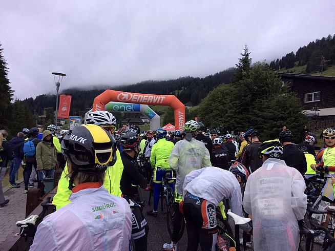 Riders huddle in the early morning mist at the start.