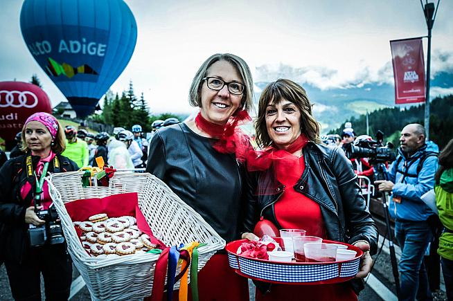 Volunteers offer samples of delicious local food at the feed stops. Photo: Sportograf