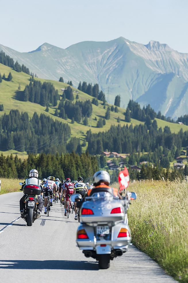 Moto outriders accompany the bunch as they roll through pristine Swiss real estate. Phil Gale / Emmie Collinge