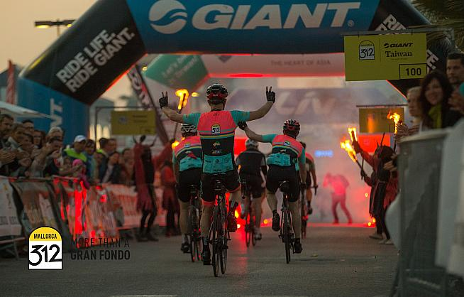 Riders cross the finish line after an epic day in the saddle on Mallorca.