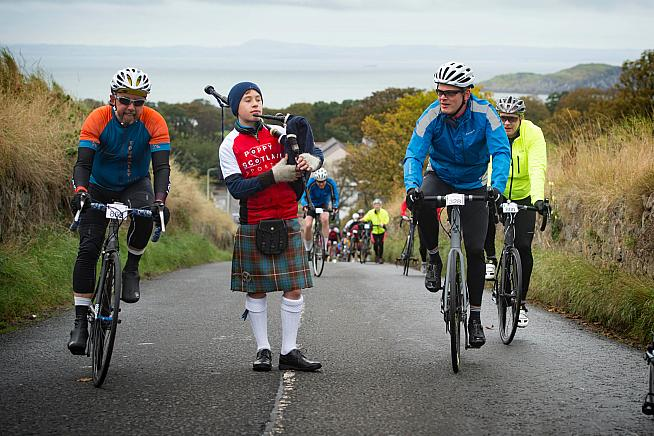 A piper encourages riders on the 'King/Queen of the Heugh' hill climb challenge.