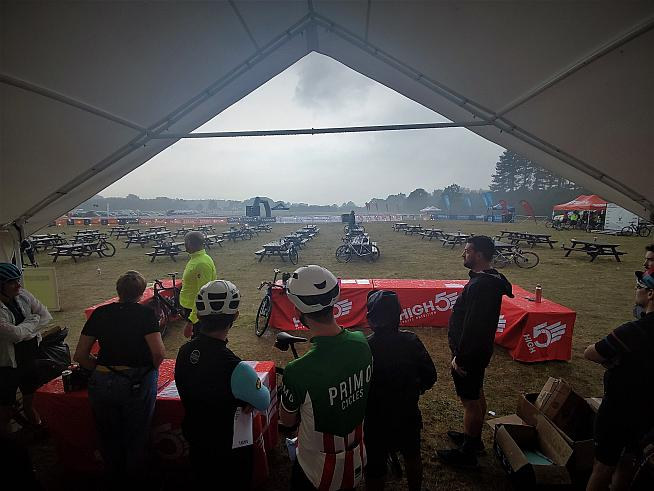 Cyclists take shelter while debating whether to ride the course anyway. Photo: Peter Levenspiel